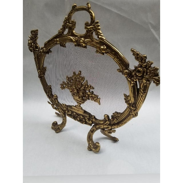 The screen is very ornate with floral and scroll work borders, scrolled feet and wreath form handle.