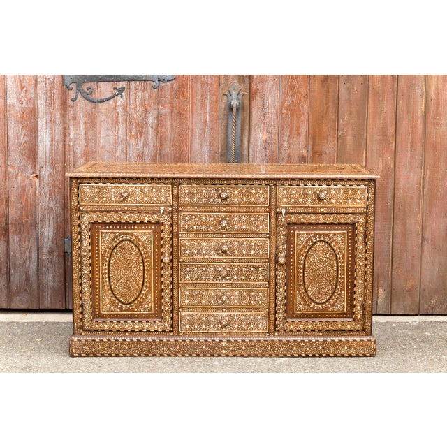 Anglo-Indian rosewood sideboard cabinet featuring a total of eight pull out drawers and two storage cabinets, each opens...