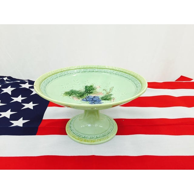 This charming pedestal dish features a classic majolica glaze. The top is embellished with a darling grape vine pattern....