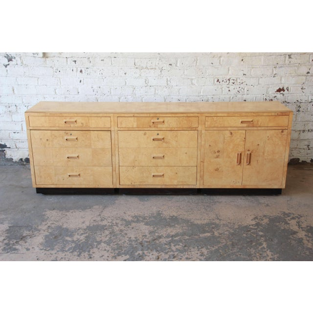Offering a stylish long burl wood credenza or bar cabinet by Henredon Furniture. The piece features three locking drawers,...