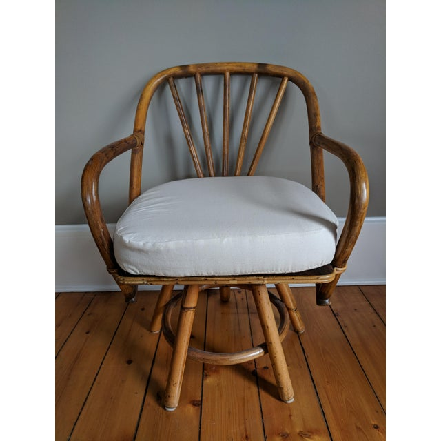 Wonderful set of four swivel dining height bamboo armchairs with linen, ivory seat cushions. These chairs bear the...