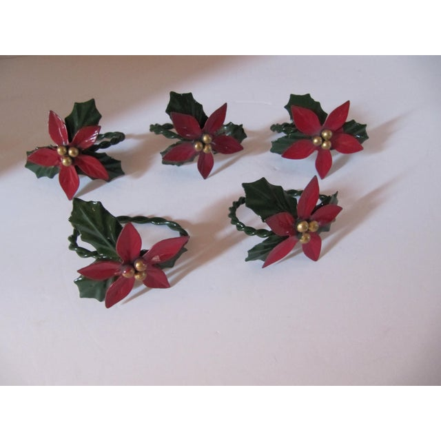 Set of 4 Christmas napkin rings decorates with holly leaves and berry designs.