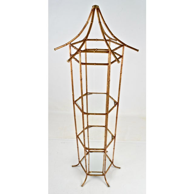 Pagoda-form tall display shelf featuring parcel gilded faux bamboo styling. Two clear glass shelves and a mirror glass...
