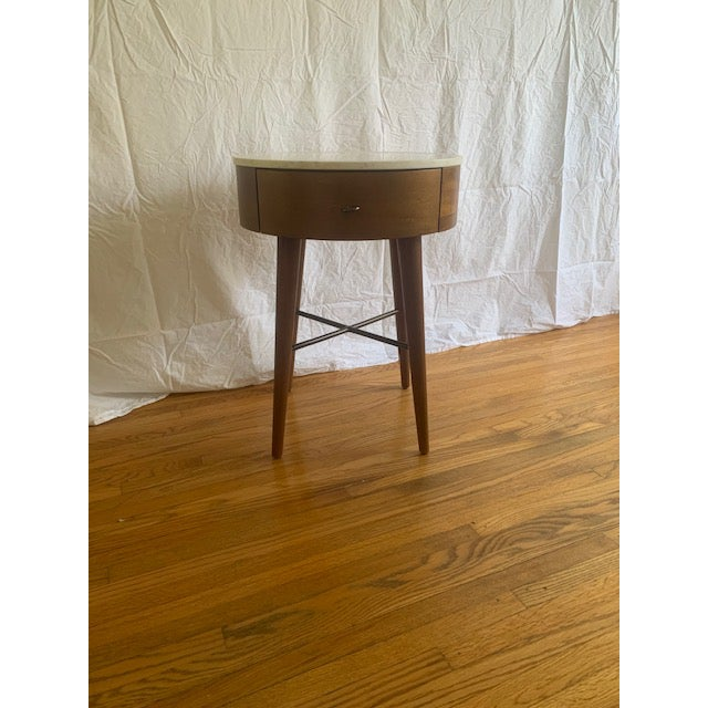 West Elm side table or nightstand. The table has a marble top, one drawer, and acorn wood. Small round metal drawer pull...