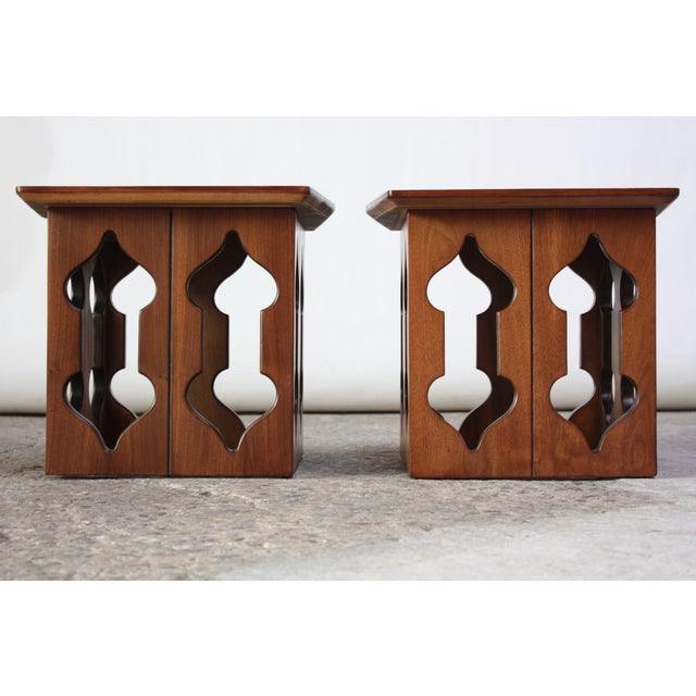 Pair of midcentury American modern walnut end or side tables with Moorish-style carved openings. Unique form and beautiful...