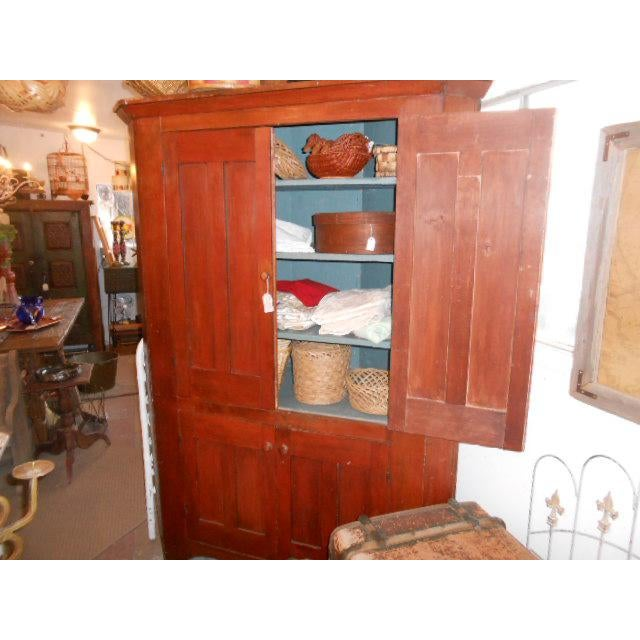 Large early American corner cupboard from the New England area. Double doors on the top and bottom. Top has 4 shelves and...