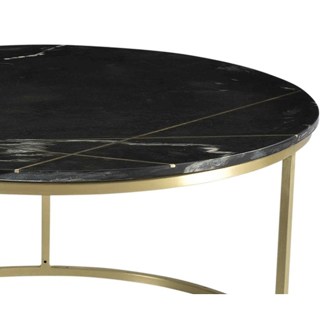 Modern round coffee table with black toned marble top and antiqued brass finish iron inset detail and base. Heavy, quality...