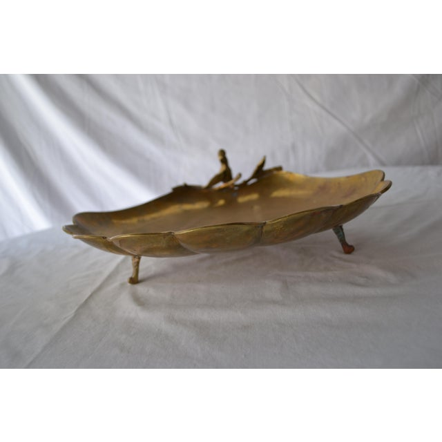 Vintage scalloped brass tray/dish on legs with a decorative bird on a branch. This has patina from age and elements, a...