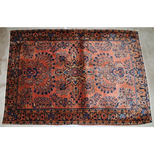 Handmade antique Persian Sarouk rug in original good condition. The rug is from the beginning of 20th century made in red...
