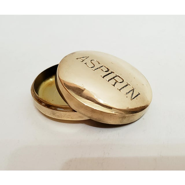 """Crazy cute vintage brass pillbox/ paperweight with the word """"aspirin"""" inscribed across the top. Includes the original..."""