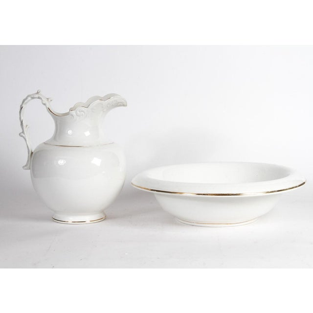 A semi-vitreous porcelain basin and pitcher. This pitcher and basin feature gold toned detail on white porcelain. The...