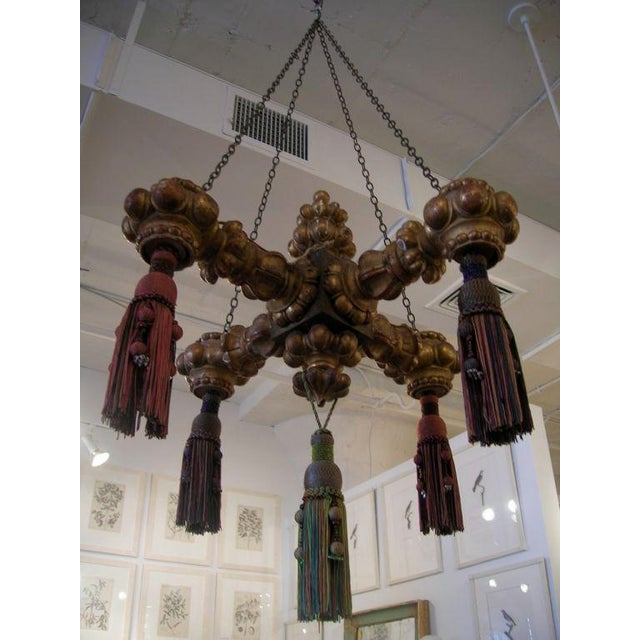 An unusual carved four-arm giltwood chandelier with tassels and retaining its original surface.