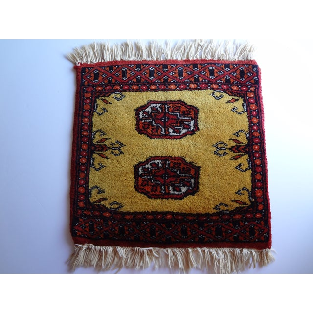 A small hand woven wool prayer rug or decorative textile. A thicker pile textile in warm gold with brick red, burnt orange...