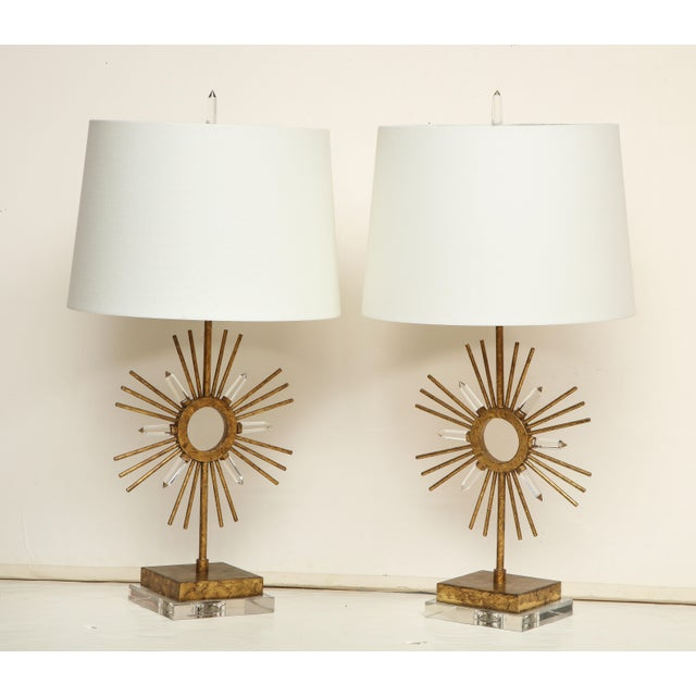 A pair of striking gilt metal lamps with a sunburst decoration on a Lucite base. Priced at $850 per lamps. Available Now