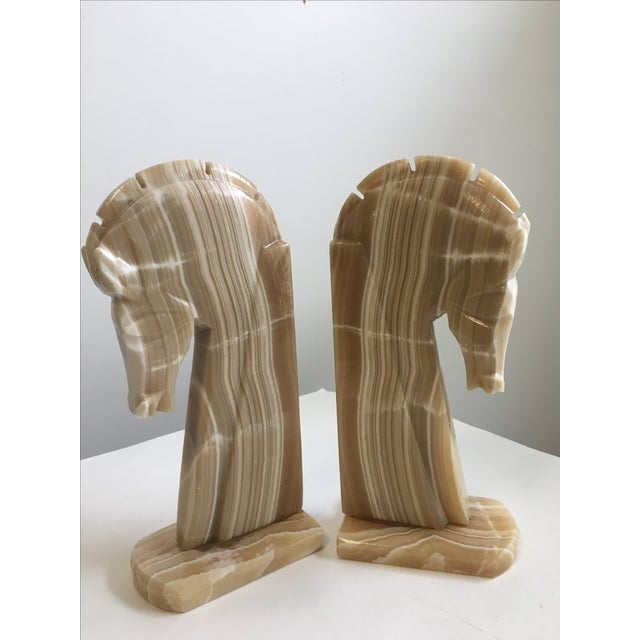 A fantastic pair of large horse bookends carved from Onyx. The stone has nice warm tones that would look great with most...