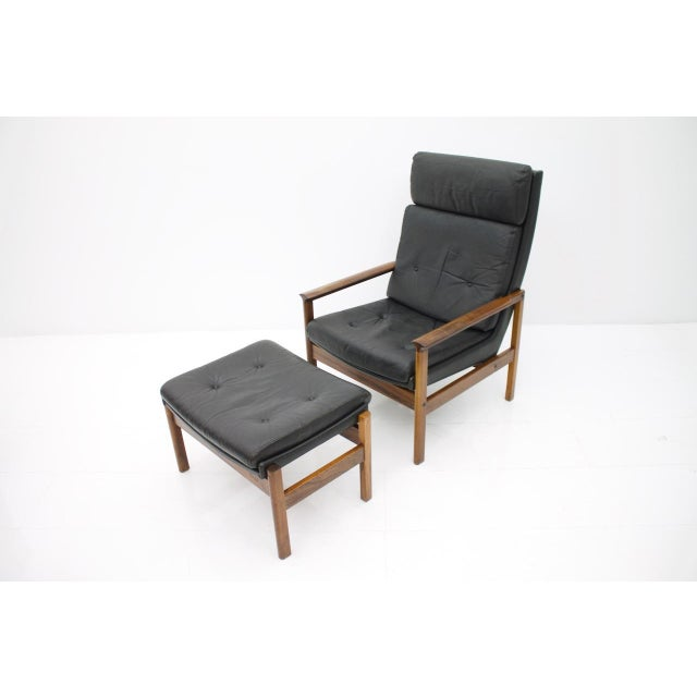 Scandinavian high back lounge chair and Ottoman in rosewood and black leather with loose cushions. The back of the...