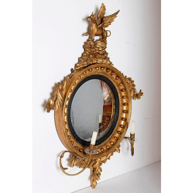 A George III gilt-wood girandole mirror with a winged mythical beast perched on a plinth of rocks above a convex mirror...