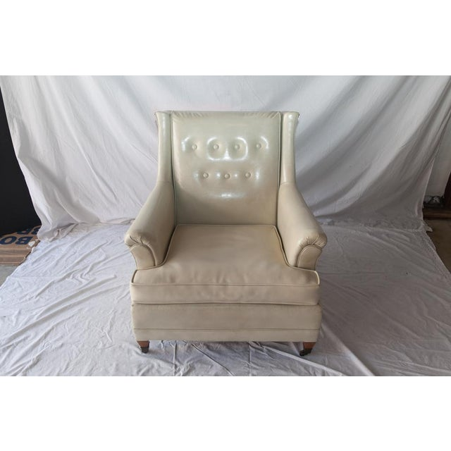 Vintage cream vinyl club chair with railheads and brass casters, from the 1950's or 60's. This is a very comfortable...