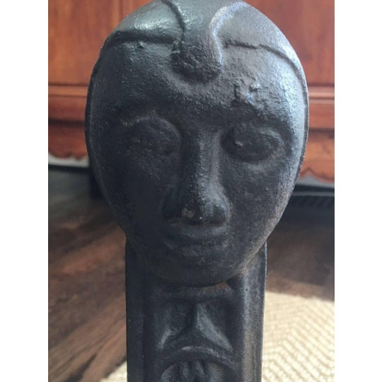 Fabulous pair of early 20th Century iron figural andirons each with figure of a lion passant at base and face at top. This...