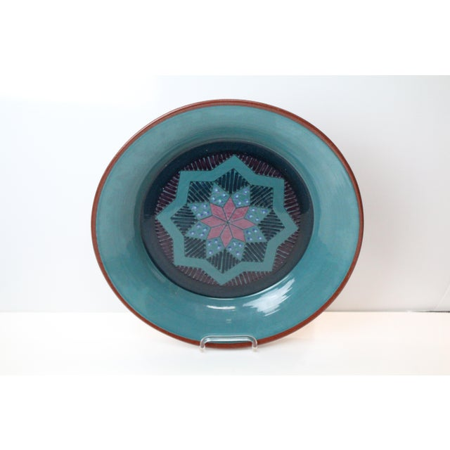 Signed Lynn Duryea of Portland, Maine handmade pottery charger in turquoise with a purple geometric design with red exterior.