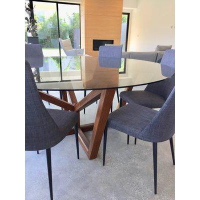 This Striking and modern dining table with a walnut base and smoked gray glass is a fabulous addition to any dining room...