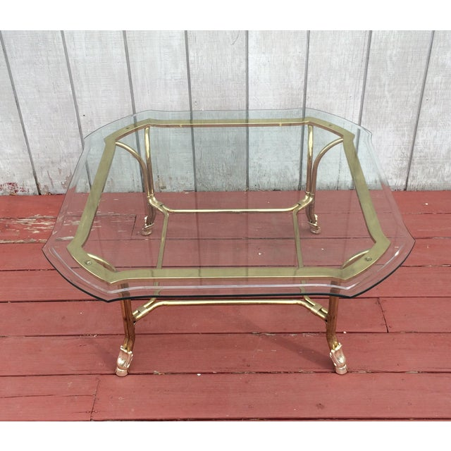 Hollywood regency style brass coated coffee table with silver coated hoof feet. Table features a heavy glass top with...