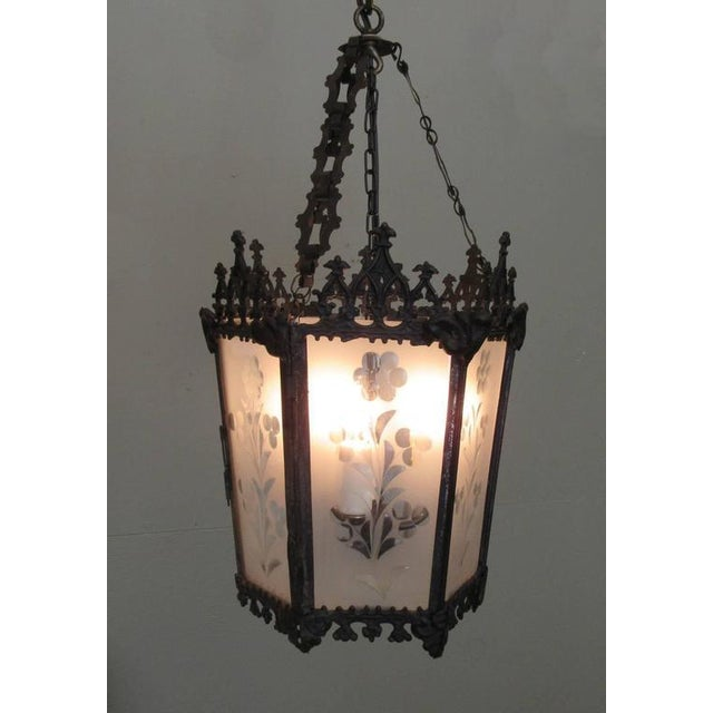 A Gothic lantern from New Orleans, circa 1850, featuring ebonized brass frame, etched glass panels and three candle bulb...