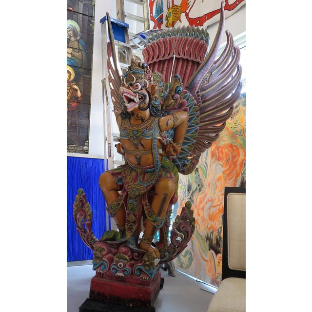 An amazing carved wooden Garuda statue. In India and Southeast Asia the eagle symbolism is represented by Garuda, a large...