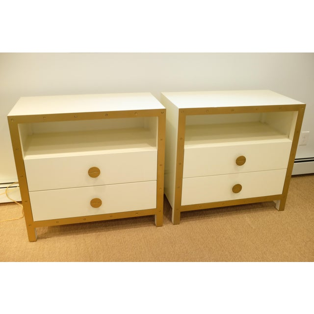 Pair of white/cream-colored nightstands or chests with double working drawers and open shelf. Brass/gold hardware...