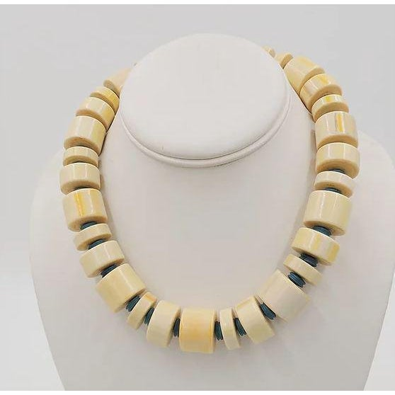 Faux-ivory beads with turquoise colored spacer beads necklace with a spring ring clasp. Marked with a Monet hang tag....