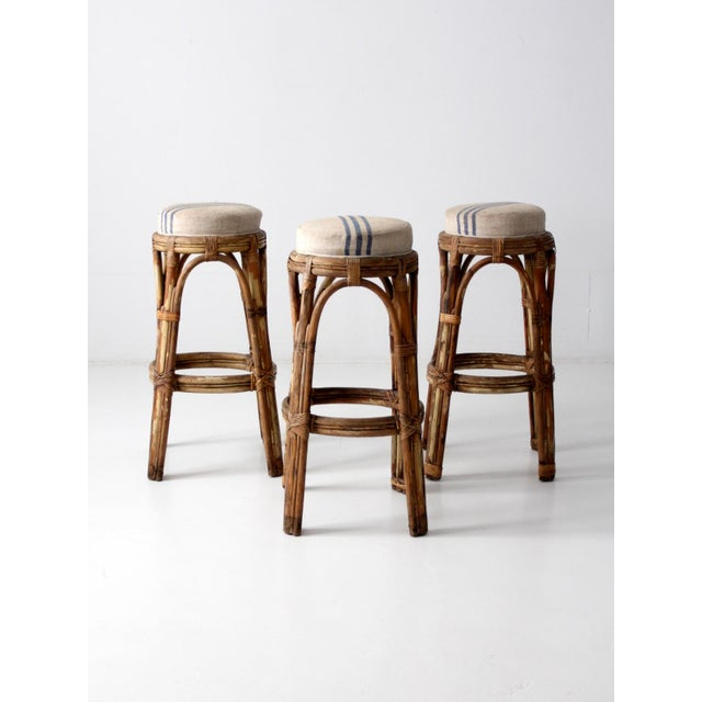 This is a set of three vintage rattan bar stools with grain sack upholstery. The mid-century stools feature bentwood...