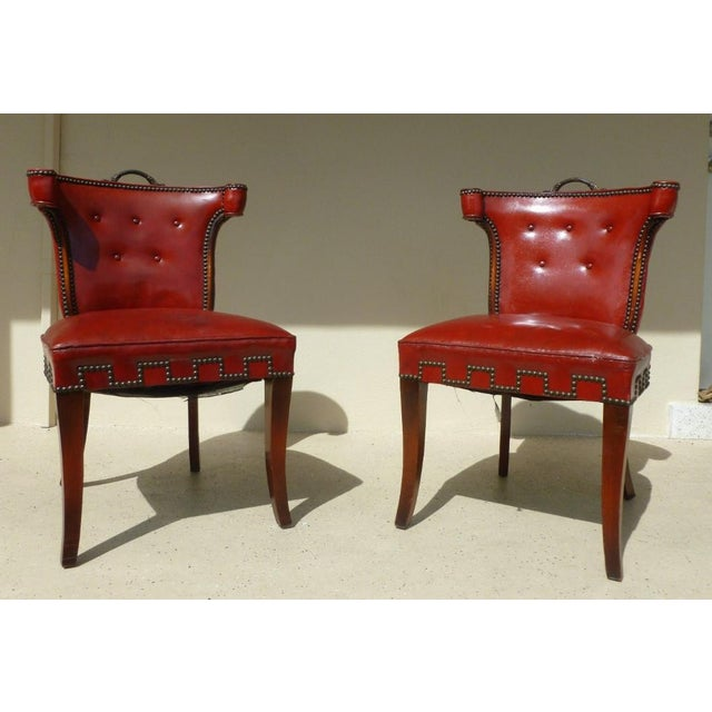 A pair of Hollywood Regency Klismos Dorothy Draper style red leather and brass tack chairs with brass handles sold as...