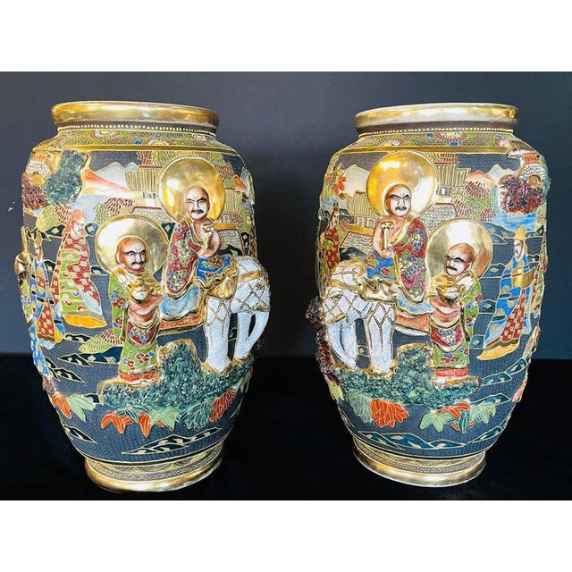 Pair of antique Japanese Satsuma vases. Each with opposing Scenes of figures and raised elephants. The pair in good...