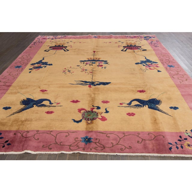A Chinese Art Deco rug with a rose border and mustard field with a floral motif. The term Art Deco refers to the style...