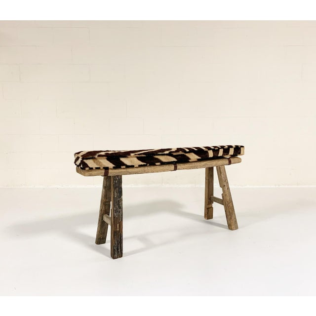 Really nice, simple-profile 19th century Chinese elmwood bench to pull up anywhere. We added a custom zebra hide cushion...