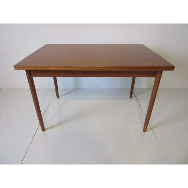 A teak wood dining table with each side having a pullout leaf , a great table for a smaller space . made in Denmark ....