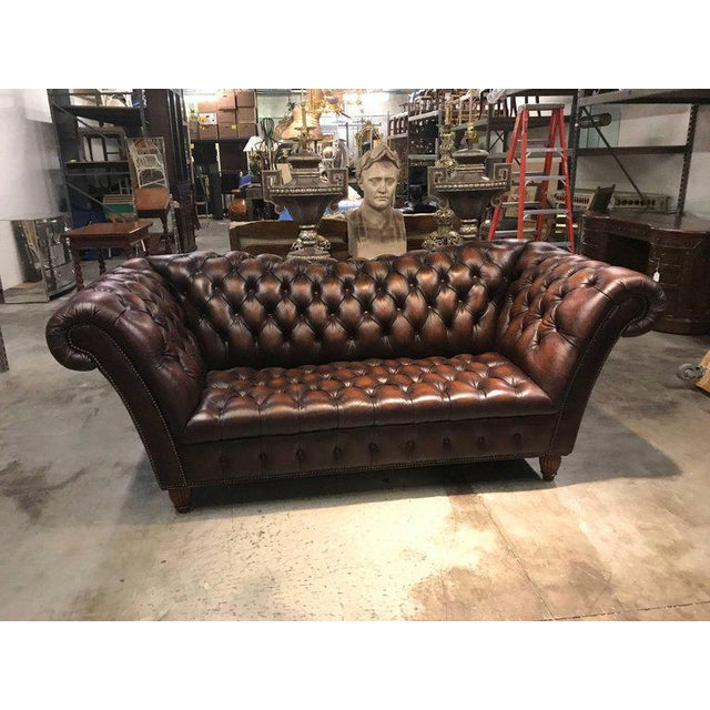 Sumptuous leather Chesterfield sofa with rolled arms raised on reeded bun feet.