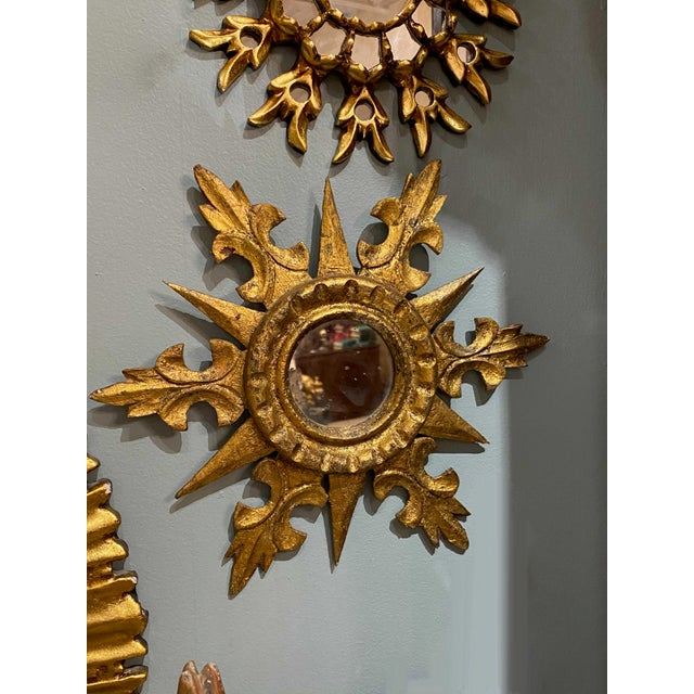 Round starburst mirror in gilt with alternating points and fleur-de-lis shapes. A smaller size that can be used in any room.
