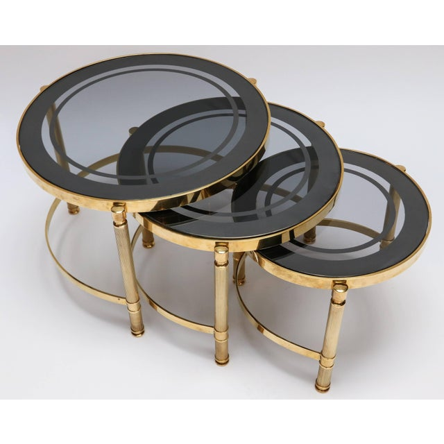 """1980s Set of three brass nesting tables with decorative details and smoked glass tops. Small: 14.75"""" dia x 11.75"""" high..."""