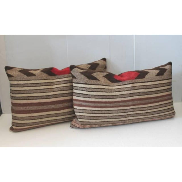 Pair of striped Navajo Saddle blanket weaving bolster pillows. Wonderful condition. These pillows have brown cotton linen...