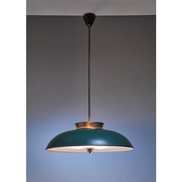 An early Modernist Swedish pendant lamp by Harald Notini made of brass with a frosted glass diffuser. Part of the shade is...