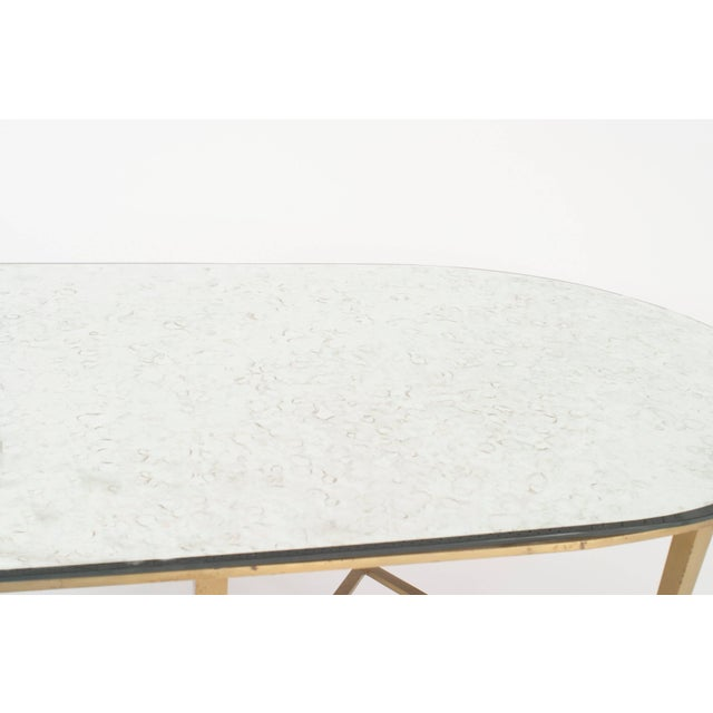 "American 1940s bronze base oval shaped coffee table with a double ""X"" design stretcher and an ""antique"" mirrored top."