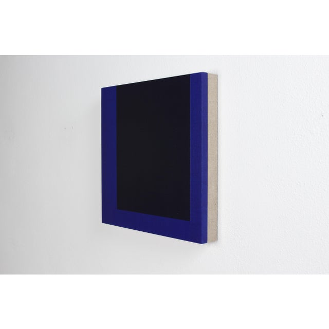 This contemporary abstract painting by American artist Brandon Woods features a rich navy blue surrounding a deep field of...