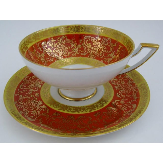 Vintage Bavarian porcelain tea cup and saucer with bands of rust and yellow against a white glaze, with a gilded floral...