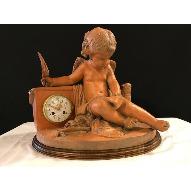 French Terracotta Cherub Clock. Unusual Mantle Clock depicting a cherub studying his writings with a bird perched on the...