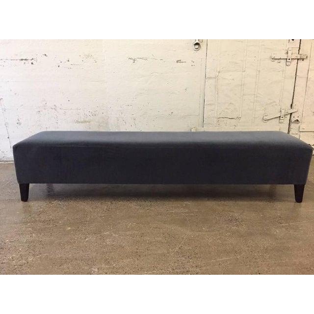 Long Art Deco upholstered bench. Upholstered in velvet with black lacquered wood legs.