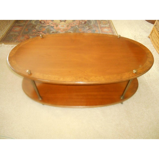 Vintage Brandt Hagerstown Maryland burl wood inlay, oval, 2 tier coffee table with brass legs and casters. The coffee...