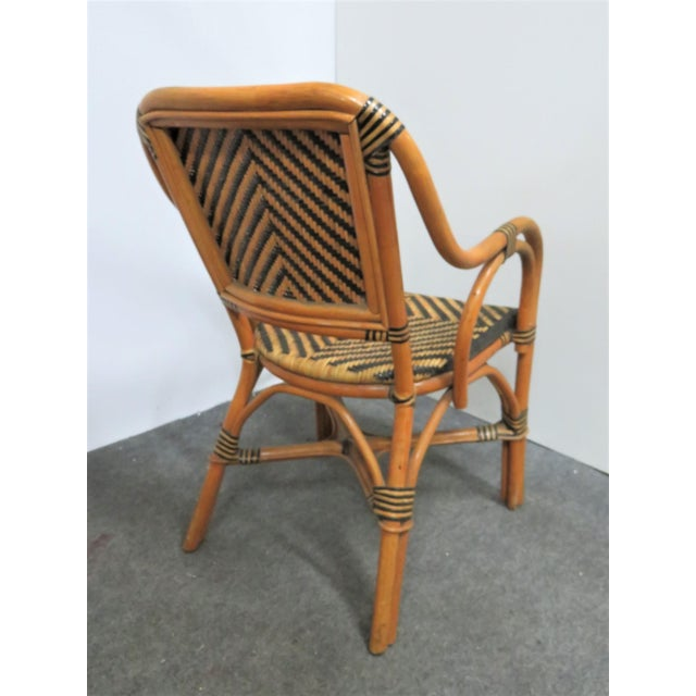 Set of 4 mid century rattan arm chairs. 2 tone black and natural finish. Basket weave pattern seat and back.
