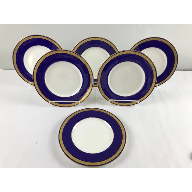Six pristine Minton plates stamped Tiffany New York with the original dish felt pads to separate them. The plates look...