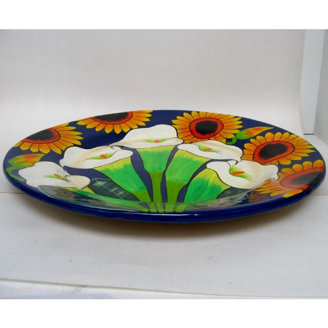 Large Mexican ceramic wall plate with hand-painted calla lilies and sunflowers against a bright cobalt background....